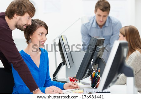 Group of young business people working in the office with focus to a young man and woman sharing a desktop monitor as they check information online against their paperwork - stock photo