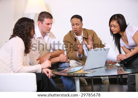 Group of young businesspeople brainstorming together with laptop