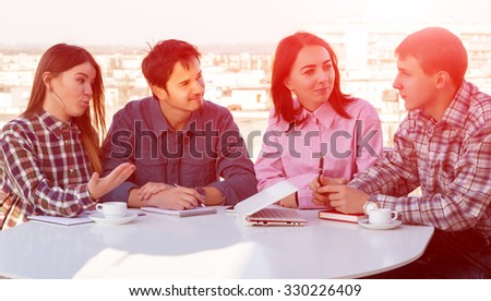 Group of Young Casual Dressed People on Informal Business Meeting at White Rounded Table Roof Top Cafe Terrace Urban Landscape Background Sun Shining - stock photo