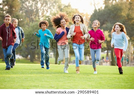 Group Of Young Children Running Towards Camera In Park - stock photo
