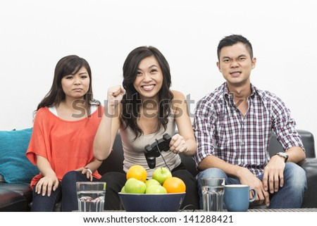 Group of Young Chinese friends playing video games at home - stock photo