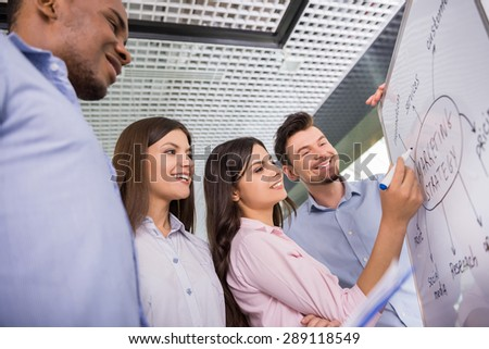 Group of young colleagues dressed casual standing together in modern office and brainstorming. - stock photo