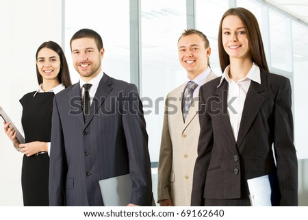Group of young colleagues goes on an office corridor - stock photo