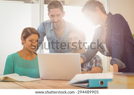 Group of young colleagues using laptop at office - stock photo