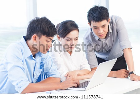 Group of young colleagues working with laptop together
