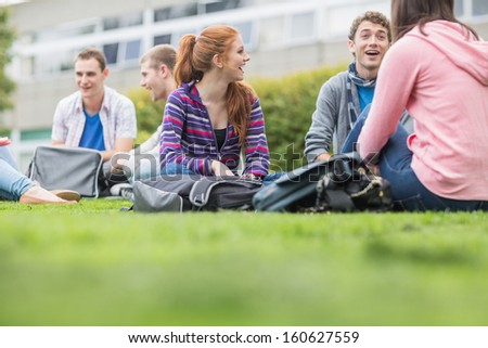 Group of young college students sitting in the park - stock photo
