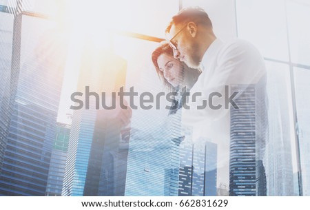 Group of young coworkers on business meeting.Business team in working process.Double exposure,skyscraper building blurred background.Flares effect