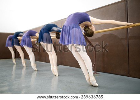 Group of young dancers doing a workout in the classroom near barre. Stretching back. - stock photo