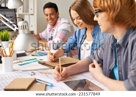 Group of young designers making sketches in office - stock photo
