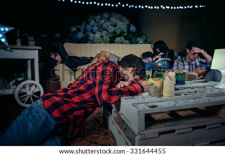 Group of young drunk and tired friends sleeping after outdoors party. Fun and alcohol and drugs problems concept. - stock photo