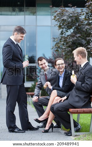 Group of young employees having lunch outdoors - stock photo