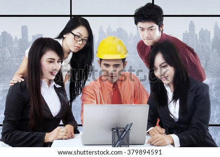Group of young entrepreneurs and architect in a business meeting, looking at the laptop computer - stock photo