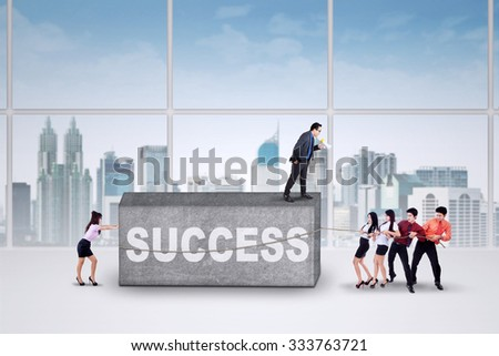 Group of young entrepreneurs work together to move an obstacle with a text of success in office - stock photo