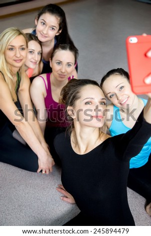 Group of young female athlete friends using mobile phone, taking picture, posing for selfie, self-portrait with smartphone while resting after practice, on break between exercises in sports club - stock photo