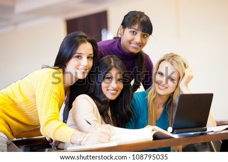 group of young female college students using laptop in classroom