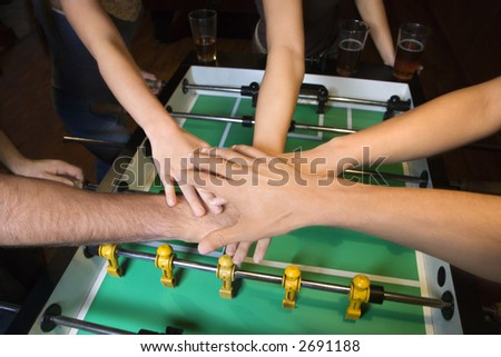 Group of young friends clasping hands in solidarity over foosball table. - stock photo