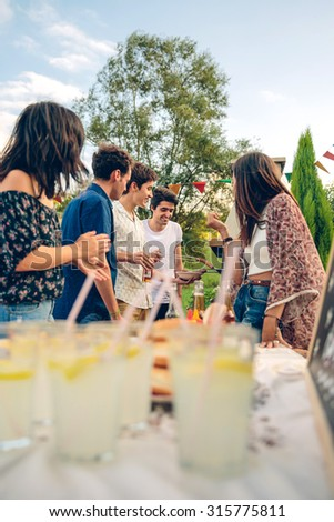 Group of young friends cooking sausages and having fun in a outdoors summer barbecue - stock photo