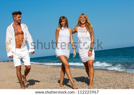 Group of young friends dressed in white wandering along sunny beach.