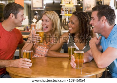 Group of young friends drinking and laughing in a bar - stock photo