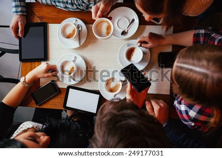 Group Of Young Friends Drinking Coffee In Cafe. View From above