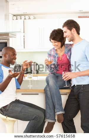 Group Of Young Friends Enjoying Glass Of Wine In Modern Kitchen - stock photo