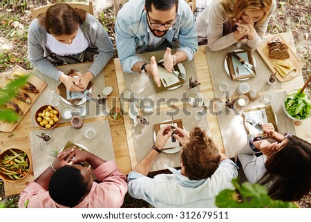 Group of young friends gathered at Thanksgiving dinner table - stock photo
