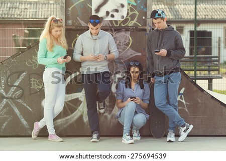 Group of young friends hanging out in a skate park and using mobile phones - stock photo