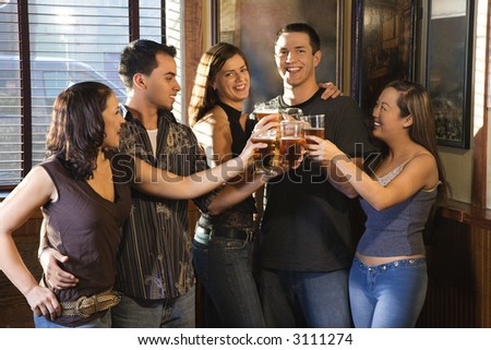 Group of young friends hanging out in pub and toasting with their beers. - stock photo