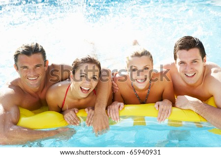 Group of Young friends having fun in pool - stock photo