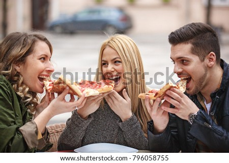 Group of young friends having fun outside and eating pizza.