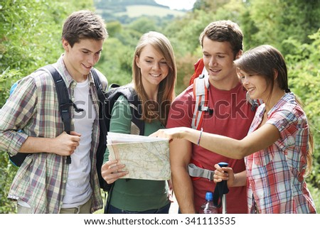 Group Of Young Friends Hiking In Countryside - stock photo
