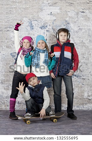 Group of young friends in casual wear against a brick wall - stock photo