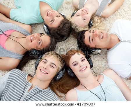 Group of young friends listening to music on the floor - stock photo