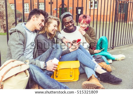 Group of young friends looking at a smart phone. Mixed race group sitting against a railing, two boys and two girls wearing casual style clothes. Friendship and lifestyle. Tone added.