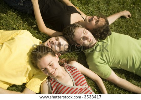 group of young friends on the grass - stock photo