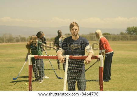 group of young friends playing field hockey - stock photo