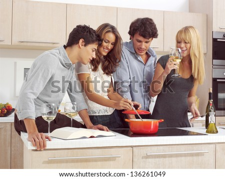 Group Of Young Friends Preparing Breakfast In Modern Kitchen - stock photo