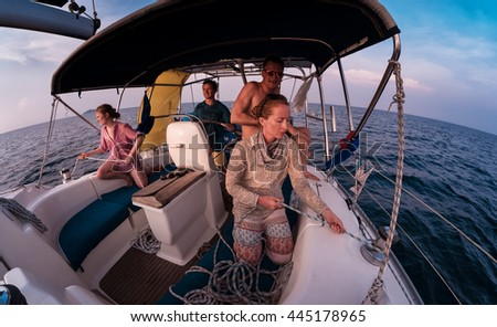 Group of young friends sailing in a open blue sea - stock photo