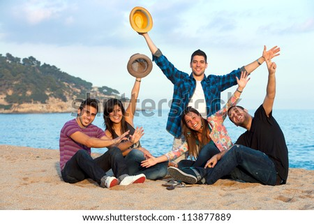 Group of young friends singing and clapping hands on beach.