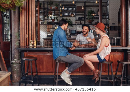 stock photo group of young friends sitting and talking at a cafe young men and women meeting in a coffee shop 457155415
