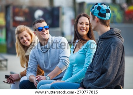 Group of young friends sitting on a park bench talking - stock photo