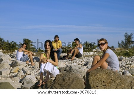 Group of young friends sitting on rocky beach