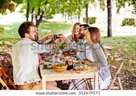 Group of young friends toasting with red wine at Thanksgiving table