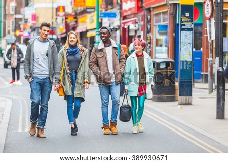Group of young friends walking in famous Brick Lane in London. Multicultural people with mixed races wearing colourful clothes having fun together. They could be students or tourists