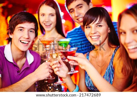 Group of young friends with cocktails looking at camera at party