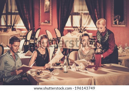 Group of young friends with menus choosing in a luxury restaurant - stock photo