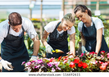 group of young gardeners working inside greenhouse - stock photo