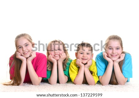Group of young girlfriends in colored T-shirts lying on the floor - stock photo