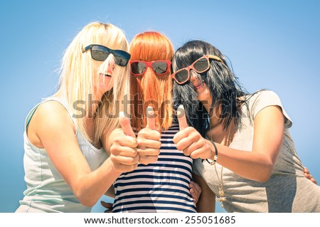 Group of young girlfriends with focus on colored funny hair and sunglasses - Concept of friendship and fun in the summer expressing positivity with thumbs up - Best friends sharing happiness together - stock photo