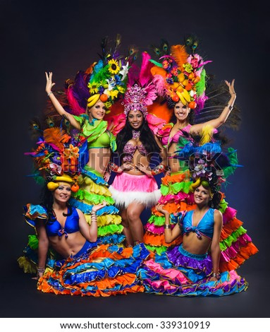 Group of young girls in bright colorful carnival costumes on dark background - stock photo